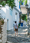 Tourist explores the alleys of Skiathos, Greece