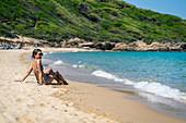 Woman enjoys the sun on Mandraki beach, Skiathos, Greece