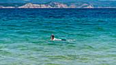 Tourist snorkels on Mandraki beach, Skiathos, Greece