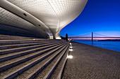 Kurz vor Sonnenaufgang auf den Stufen des MAAT (Museum) mit Blick auf den Tejo und die Ponte 25 de Abril in Lissabon, Portugal