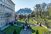 View of the tourists and Hohensalzburg Castle in the Mirabell Gardens in Salzburg, Austria