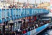 Locals fish on the Galata Bridge in Istanbl, Turkey
