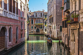 Gondolier drives tourists through the canals of Venice, Italy