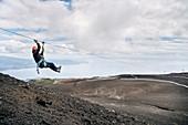 Woman practices zip lining on the Osorno volcano, Llanquihue Lake, Region de los Lagos, Chile, South America
