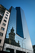 The historic cathedral of Santiago de Chile, Chile, South America is reflected on the glass facade of a high-rise building