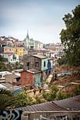 Polizei stürmt ein heruntergekommenes Viertel, Streetart, bunter Häuser und Kirchturm in Valparaiso, Chile, Südamerika