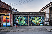People jog on sidewalk, street art in the streets of Valparaiso, Chile, South America