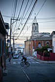 Cyclists looking to the harbor with church tower, Valparaiso, Chile, South America