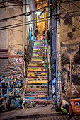 colorful stairs, young loving couple, street art in the streets of Valparaiso, Chile, South America
