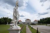 Blick auf das Schloss Nymphenburg, im Vordergrung eine Statue aus dem Garten der Götter, München, Bayern, Deutschland, Europa