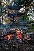 Ein Lagerfeuer bei einem Baumhaus, München, Bayern, Deutschland, Europa