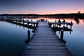 Blick auf einen Steg am Starnberger See bei Sonnenuntergang, im Hintergund Starnberg bei München, Starnberg, Bayern, Europa