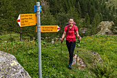 Hiker at signpost in Valle di Peccia, Trekking del Laghetti Alpini, Ticino, Switzerland