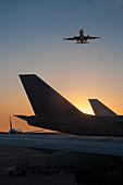 Flugzeug fliegt über Flugzeug auf Landebahn bei Sonnenuntergang