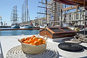 France, Herault, Sete, Escale a Sete Festival, Orange breadbasket into a basket on the deck of a sailboat with port and boats in the background