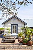 Tisch mit Bank auf Terrasse vor Holzhaus, NSW, Australien