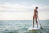 France, Morbihan, Peninsula of Quiberon, Saint-Pierre Quiberon, young woman on a paddle in the bay of Quiberon
