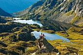 France, Ariege, Auzat, Bassies, young girls on a rock admiring a landscape of mountain lakes