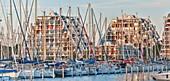 France, Herault, La Grande Motte, buildings in wave and harbor of the seaside resort