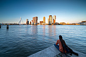 Evening view over the New Maas to the Erasmus Bridge and the skyline at the cruise terminal in Rotterdam, Netherlands.