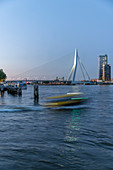 View of the Erasmus Bridge with a water taxi in the foreground during the blue hour over the New Maas, Rotterdam, Netherlands.