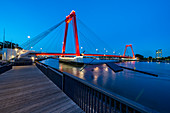 Illuminated, red Willemsbrücke during the blue hour, with plank path and seating on the river bank. Rotterdam, The Netherlands, June 2020