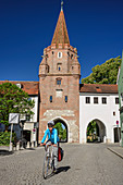 Woman rides a bicycle through city gate in Ingolstadt, Kreuztor, Ingolstadt, Danube Cycle Path, Upper Bavaria, Bavaria, Germany