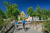 Man and woman ride a bike over bridge to the New Castle in Ingolstadt, Ingolstadt, Danube Cycle Path, Upper Bavaria, Bavaria, Germany