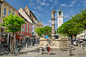 Woman cycling while sitting at fountain and reading, Straubing town square, Straubing, Danube Cycle Path, Lower Bavaria, Bavaria, Germany
