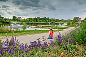 Woman cycling while sitting at ferry station, Mariaposching, Danube Cycle Path, Lower Bavaria, Bavaria, Germany