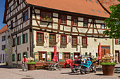 Woman rides past half-timbered house, Friedingen an der Donau, Danube Valley, Danube Cycle Path, Baden-Württemberg, Germany