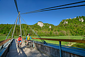 Man and woman ride a bike over bridge in the Upper Danube Valley, near Beuron, Upper Danube Valley, Danube Cycle Path, Baden-Württemberg, Germany