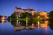 Sigmaringen Castle, illuminated, reflected in the Danube, swan in the foreground, Sigmaringen, Danube Cycle Path, Baden-Württemberg, Germany