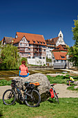 Woman cycling sits on rock and looks at half-timbered houses and Danube, Riedlingen, Danube Cycle Path, Baden-Württemberg, Germany