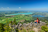 Woman hiking sits on rock and looks at Forggensee and Bannwaldsee, Tegelberg, Ammergau Alps, Swabia, Bavaria, Germany