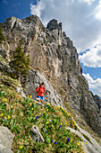 Woman hiking hikes to Geiselsteinjoch, Geiselstein in the background, Ammergau Alps, Swabia, Bavaria, Germany