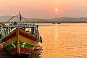 Boot mit Farben der Flagge von Myanmar am Ufer des Irrawaddy Fluss zum Sonnenuntergang, Bagan, Myanmar