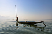 Fisherman on small boat with long stick for fishing on Inle Lake, Heho, Myanmar