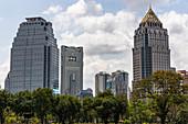 Sicht vom Lumphini Park auf Hochhäuser in Silom, Bangkok, Thailand