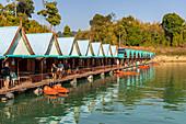 Sicht über Steg mit Bungalows (Khao Sok Smiley Lake House) auf dem Wasser des Ratchaprapha See im Khao Sok Nationalpark, Khao Sok, Thailand