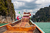 Longtail boat ride on Ratchaprapha Lake with high karst rocks in Khao Sok National Park, Khao Sok. Thailand