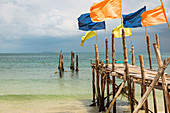 Jetty with colorful flags on Ao Wai beach, Koh Samet, Thailand