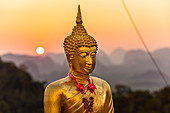 Buddha statue at sunset on Tiger Cave Mountain, Tiger Cave Temple, Krabi Town, Thailand