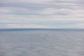 Expansive view of ocean, horizon and clearing storm clouds, dusk