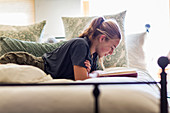 13 year old girl lying in her bed reading by window light