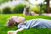 5 year old boy lying down on lush green lawn looking up