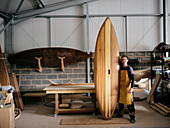 Portrait of man holding hand made wooden paddleboard in workshop