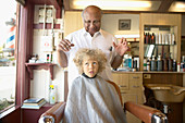 Barber examining young boy's wild hair