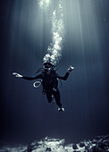 Underwater view of diver wearing wetsuit, diving goggles and oxygen cylinder, air bubbles rising.