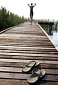 Rear view of woman wearing swimsuit walking along a jetty, hands on head, pair of flip flops in the foreground.